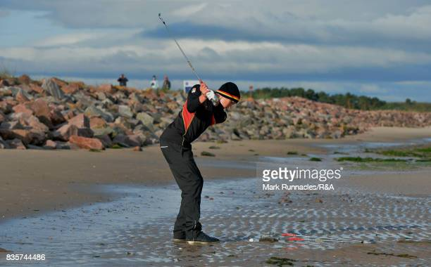 Falko Hanisch of Germany plays his second shot to the first hole from the beach that runs parallel to the first fairway during the first round of the...