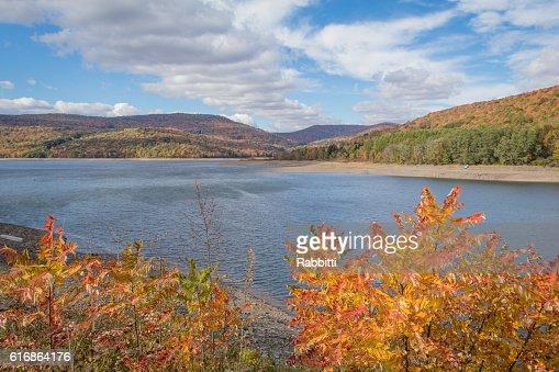 Fall foliage in peak overlooking reservoir : Stock Photo