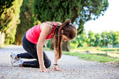 Young woman falling while jogging outdoors on a gravel road.