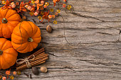 Fall pumpkin background with holiday decoration cinnamon and nutmeg on rustic wood background.
