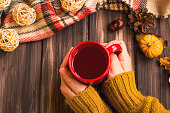 Fall setting woman hands holding hot tea cup with vintage fall blanket on wooden background and pumpkin deco,cosy autumn flatlay setting