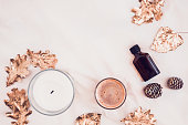 Fall spa beauty products from above on white bed sheets. Copy space for text