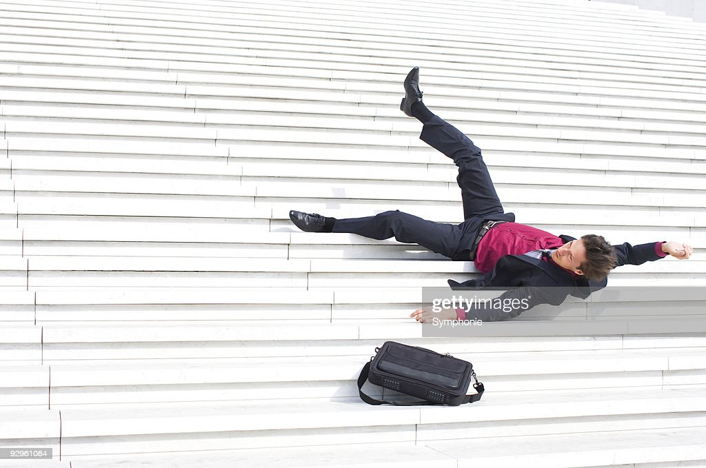 Fallen business man lying on steps : Stock Photo