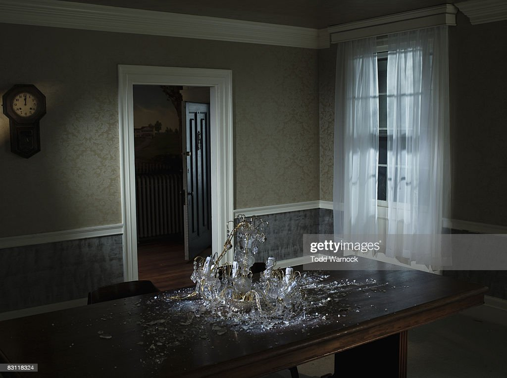 fallen chandelier on dining room table : Stock Photo