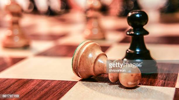 Fallen chess pawn on chess board