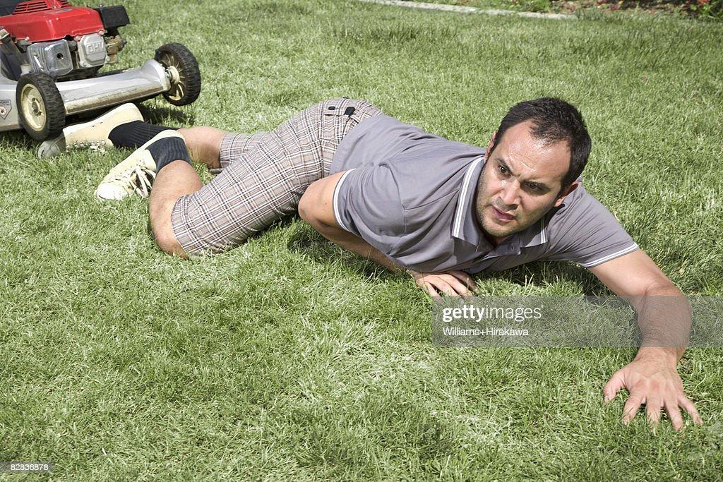 Fallen man in front of lawnmower
