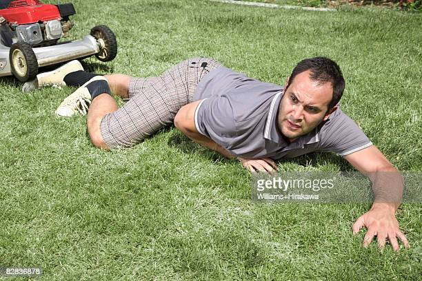 Fallen man in front of lawnmower
