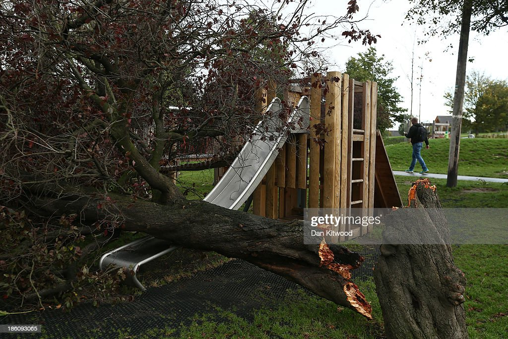 A fallen tree pictured on a slide in a children's play area in Brockwell Park on October 28, 2013 in London, England. Approximately 220,000 homes are without power and two deaths have been recorded after much of southern England has been affected by a severe storm. Transport links on road, rail, air and sea have been severely disrupted by hurricane-force winds that have almost reached 100 mph in places.