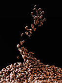 falling coffee beans on pile isolated on black