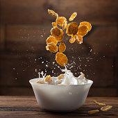 Falling breakfast flakes with milk splash on wooden background