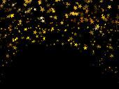 Falling golden confetti stars on black background
