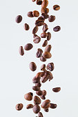 Grains of roasted coffee falling on white background, studio light