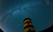 A falling star crosses the night sky behind the lighthouse in Pilsum northwestern Germany during the peak in activity of the annual Perseids meteor...