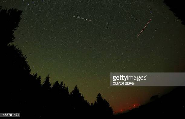 A falling star crosses the night sky near Gemuend western Germany as the trace of an airplane also can be seen during the peak in activity of the...