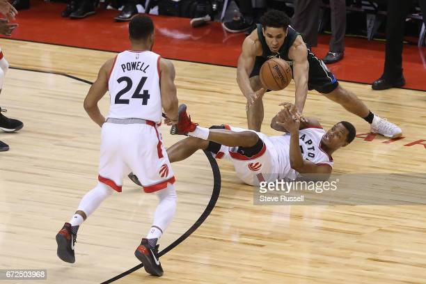 TORONTO APRIL 24 Falling Toronto Raptors guard Kyle Lowry makes a pass to Norman Powell as Milwaukee Bucks guard Malcolm Brogdon looks for the ball...