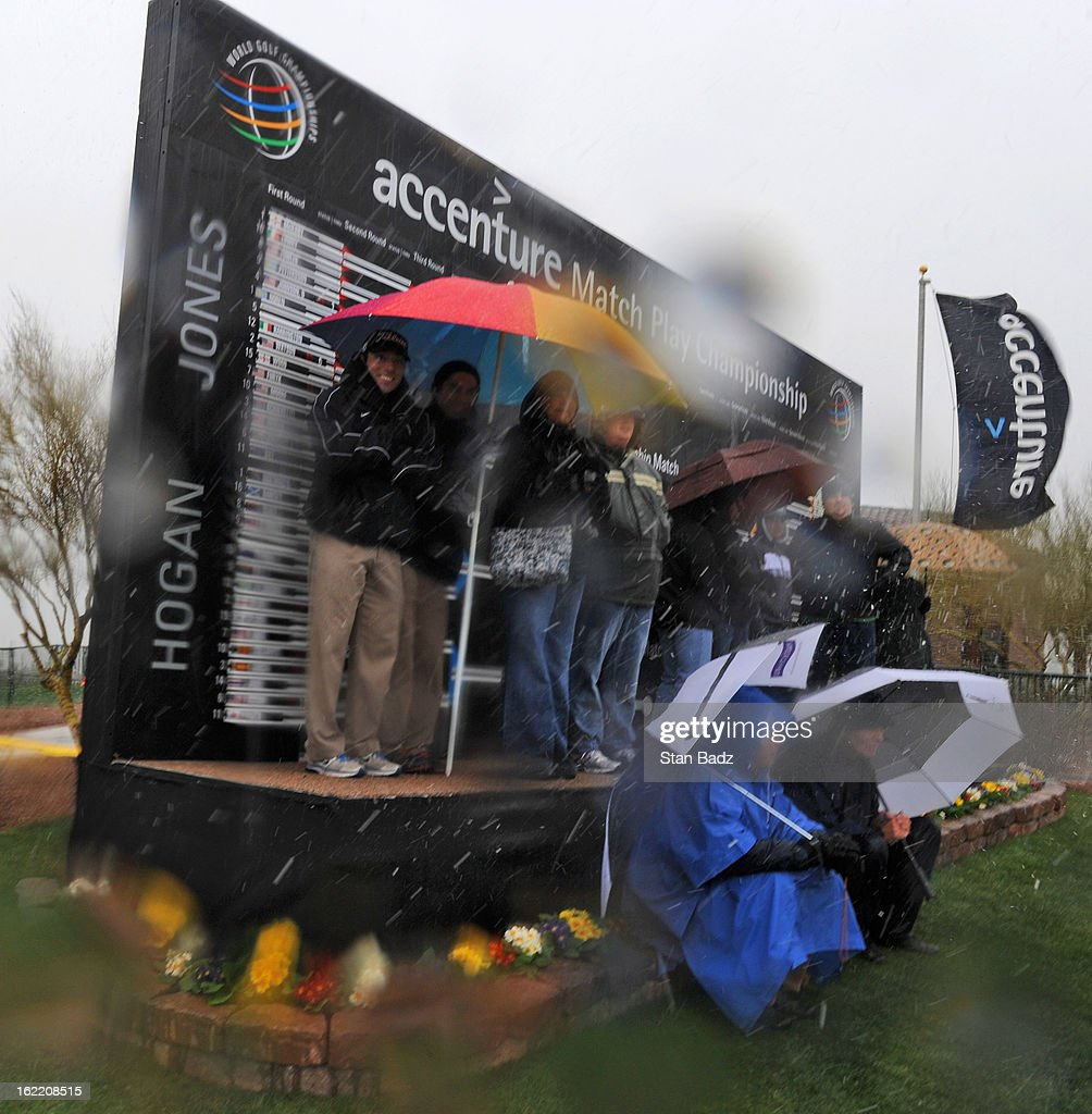 Falls huddle in front of a leader board for cover as snow and rain caused play to be suspended due to weather during the first round of the World Golf Championships-Accenture Match Play Championship at The Golf Club at Dove Mountain on February 20, 2013 in Marana, Arizona.