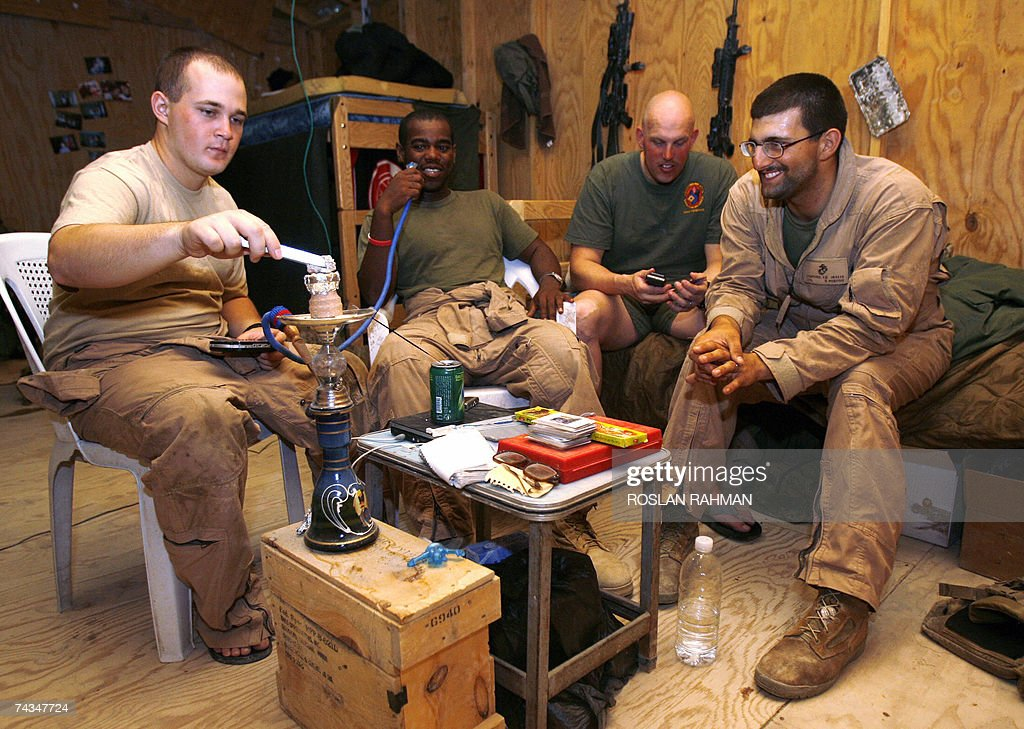 US marines Lcpl Speir PFC Harris Sgt Williams and Lcpl Bickford with the 2/6 Battalion Golf Company ECP 7 smoke waterpipe during a break at their...
