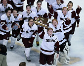 Falmouth's Kelly Ferreia hoists the trophy after she and her teammates beat Wellesley in overtime giving them a 32 victory and the state championship...