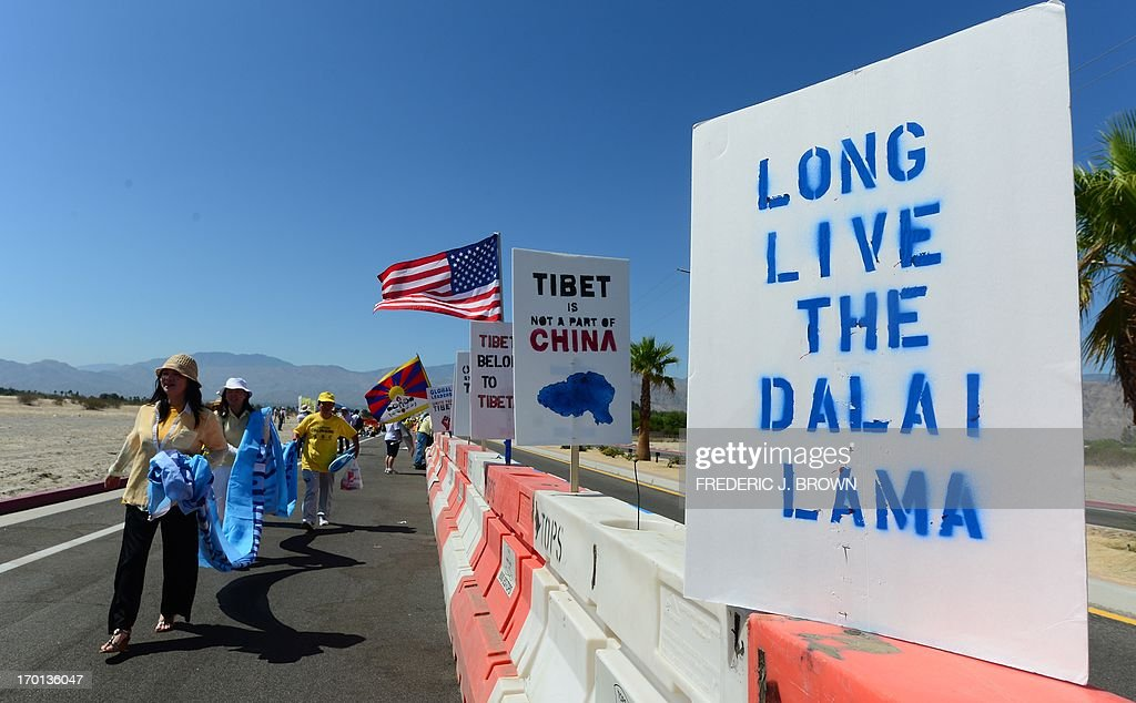 Falungong practioners walk past placards setup by protesters for the Tibetan cause on a barricade in a cordoned off protest zone across from where President Barack Obama is due to meet his Chinese counterpart Xi Jinping in the California desert community of Rancho Mirage, a little over 100 hundred miles east of Los Angeles, on June 7, 2013, where they were joined by Falun Gong practioners in protesting the brutal repression of China's ruling Communist Party. Xi, the Chinese leader arrived in southern California the previous evening and stayed in a nearby hotel, according to the local Desert Sun newspaper, ahead of what was planned as an unusually relaxed US-China summit. AFP PHOTO/Federic J. BROWN