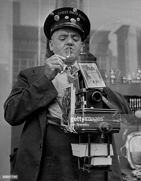 Famed news photographer Weegee aka Arthur Fellig lighting up a cigar while hamming it up as a streetcameraman for the movie Every Girl Should Be...