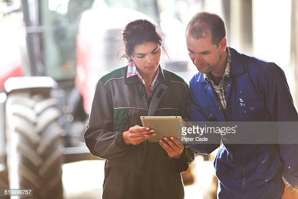 famers couple on farm  looking at a tablet.