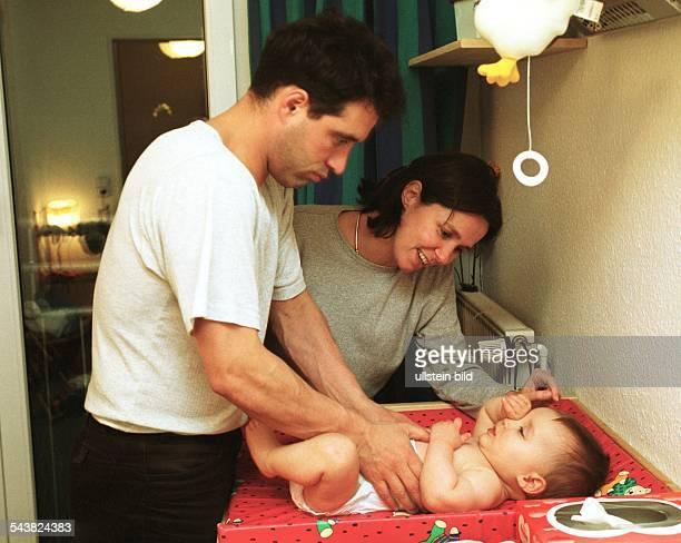 Der Vater legt seinem Kind eine neue Windel an während die Mutter nebem dem Wickeltisch steht Säugling