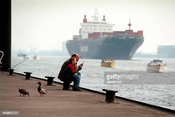 Familienidylle auf dem Anleger Op''n Bulln in Blankenese Auf einem der Poller sitzt ein Vater mit seinem Sohn in der Sonne Beide essen ein Eis am...