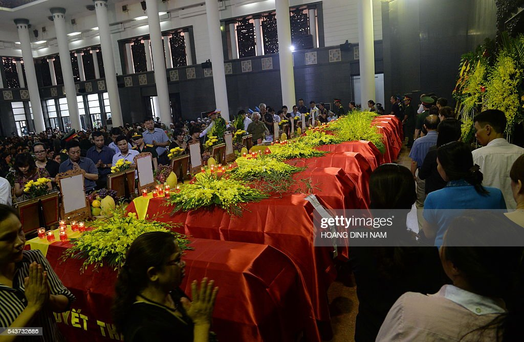 Families and friends pay tribute to the victims of a rescue aircraft that crashed on June 16, 2016 over the South China Sea during a search mission for a Vietnamese Airforce Sukhoi SU-30MK2 that went missing two days earlier, during an official funeral ceremony in Hanoi on June 30, 2016. / AFP / HOANG