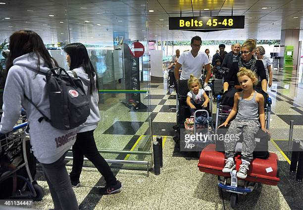 Families arrive at Changi International Airport after their Singapore Airlines Airbus A380 relief plane landed in Singapore on January 7 2014...