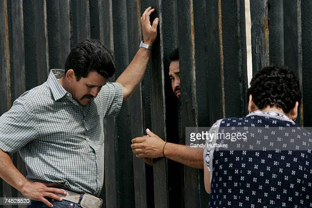 Families converse through the US and Mexico border wall June 10 2007 in San Ysidro California President Bush will meet with key Senators this week in...