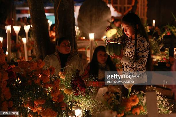 Families decorate a relative's grave with flowers at a cemetery in Tzintzuntzan Michoacan State Mexico on November 1 2015 during the commemoration of...