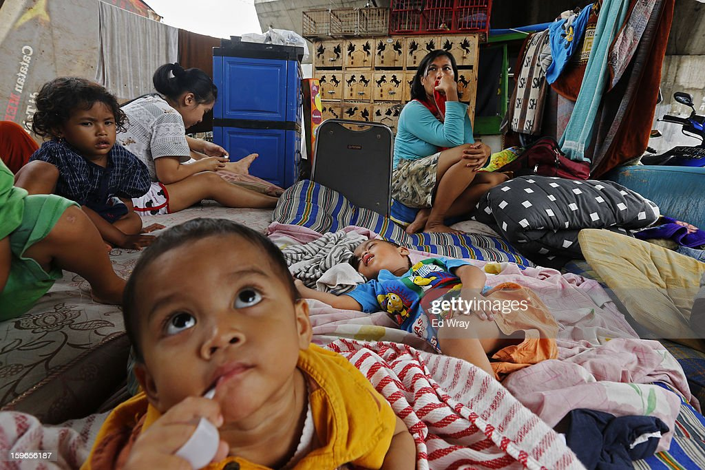 Families, displaced by flooding, sit among salvaged household goods at a temporary refuge under a highway flyover on January 18, 2013 in Jakarta, Indonesia. According to the National Disaster Management Agency, about 50 percent of the capital is under water following the floods which have so far claimed eleven lives and displaced thousands of Indonesians.