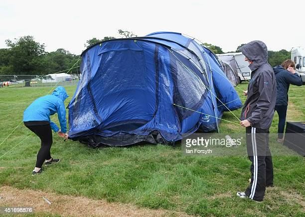 Families erect their tents during a rain shower in the grounds of Harewood House in Yorkshire as visitors get ready for the start of the Yorkshire...