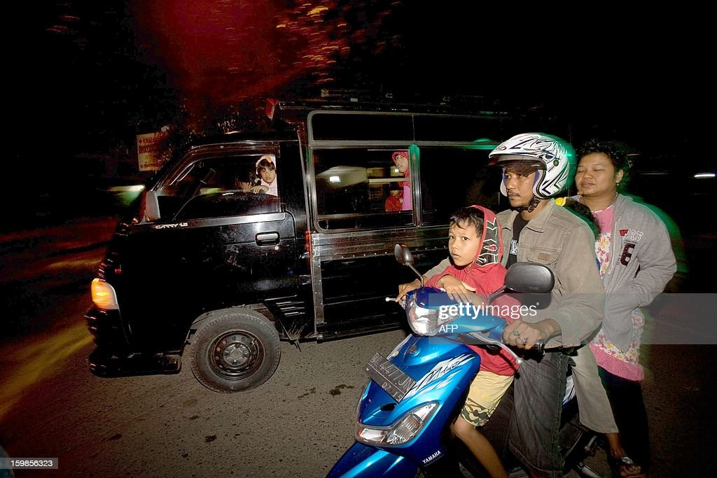Families flee on motorcycles and cars to higher grounds in the capital Banda Aceh following a 5.9-magnitude earthquake that struck off Indonesia's Aceh province early January 22, 2013, killing an eight-year old girl and injuring seven others, officials said, as panicked residents rushed outdoors. The quake struck 112 kilometres (70 miles) southeast of provincial capital of Banda Aceh at 22:22 GMT at a depth of 37 kilometres, the US Geological Survey said.