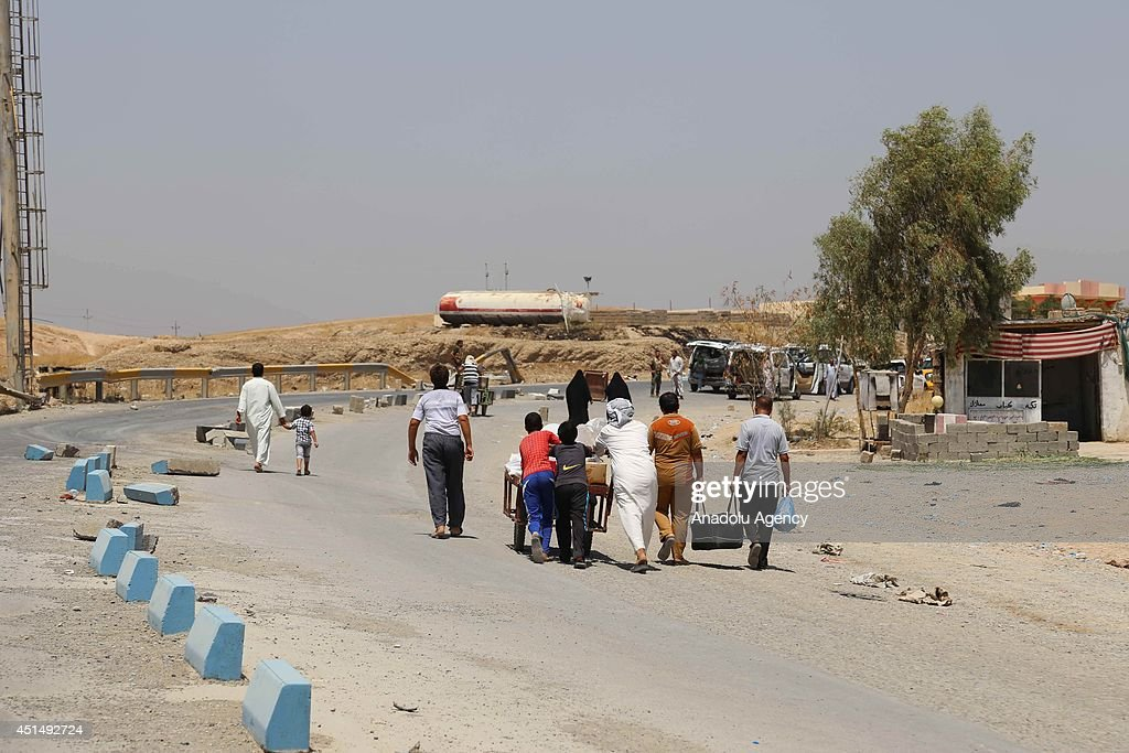 Families fleed from clashes between army groups led by Islamic State of Iraq and the Levant and peshmargas and pass to secure Kurd region by walking on 40 degree temperature and they also fast in Ramadan in Sulaymaniyah, Iraq on 29 June, 2014.