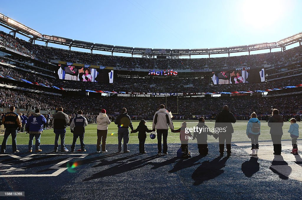 Families from Sandy Hook Elementary School in Newtown, Connecticut surround the field during the national anthem before the game between the New York Giants and the Philadelphia Eagles at MetLife Stadium on December 30, 2012 in East Rutherford, New Jersey.