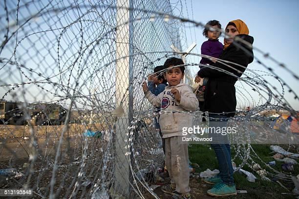 Families gather at the barbed wire fence fence at the GreekMacedonia border on March 01 2016 near Idomeni Greece The transit camp has become...