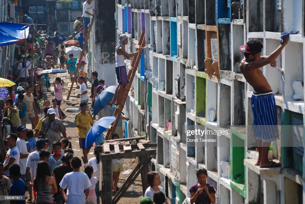 Families gather to pray, light candles and clean tombstones of the departed at the Navotas public cemetery on November 1, 2011 in Manila, Philippines. The 'Day of the Dead (Todos Los Santos), 'All Saints' Day,' and 'All Souls Day' are feast days celebrated on the first and second of November each year in Latin cultures around the world during which family and friends of the deceased gather at cemeteries to pray and hold vigils for those who have passed. In the Philippines, family members clean the tombs, leave flowers and often spend the night at the tomb eating and celebrating with loved ones.