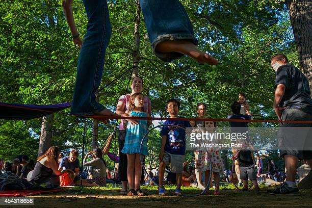 WASHINGTON DC JUNE Families gather to watch tightrope walkers and listen to the music of the park's historic African drum circle at Meridian Hill...