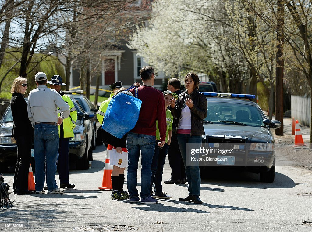 Families get back to their routine as law enforcement investigators continue collecting and processing evidence at the shooting scene near a boat...
