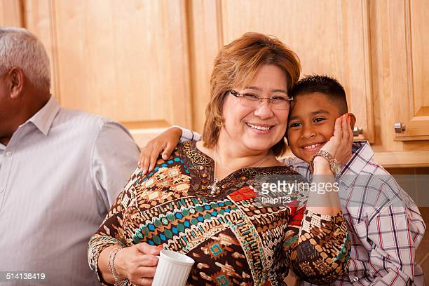 Families: Grandmother and grandson hug during family gathering.