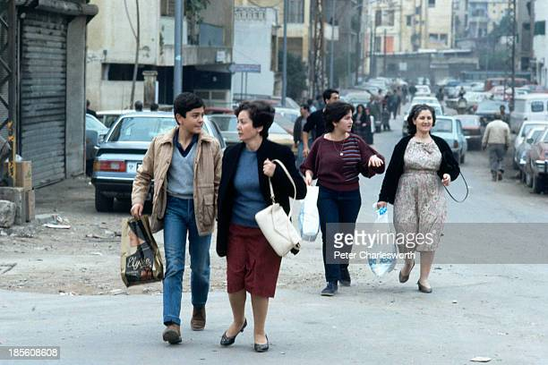 Families hurry down a war torn street as shells continue to fall and gunfire erupts nearby Lebanese civilians fled random shelling and street...