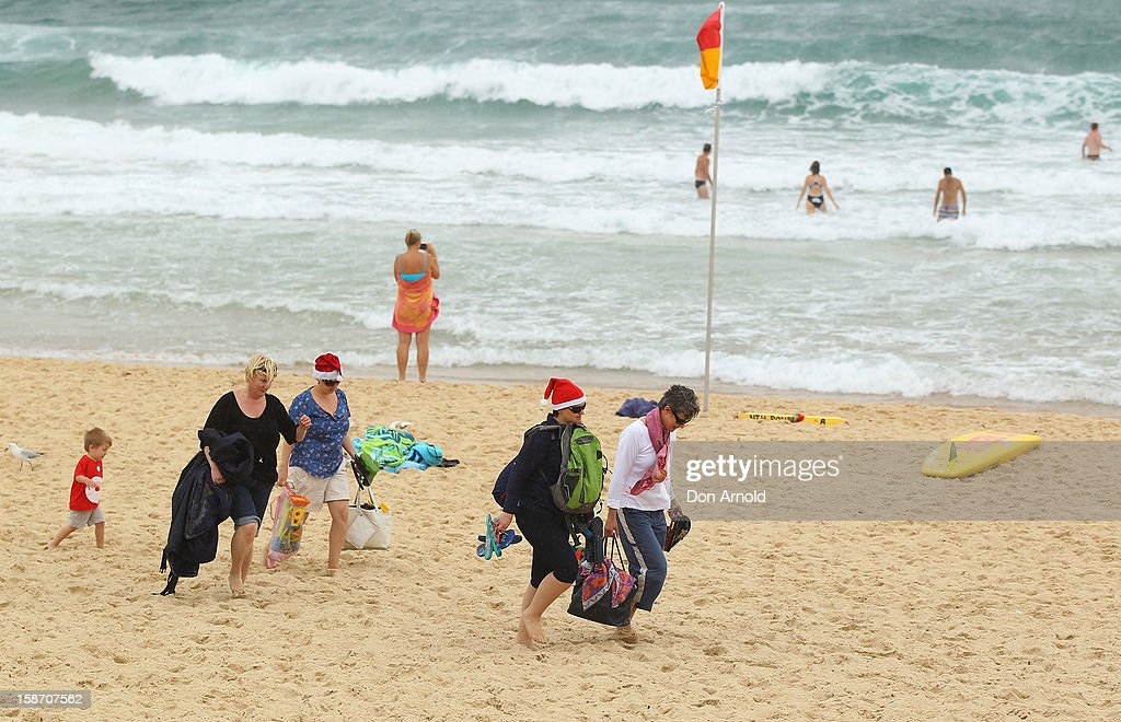 Families make their exit as a storm hits Bondi Beach on December 25, 2012 in Sydney, Australia. Traditionally beaches such as Bondi Beach are popular destinations for tourists and locals alike to celebrate Christmas Day.