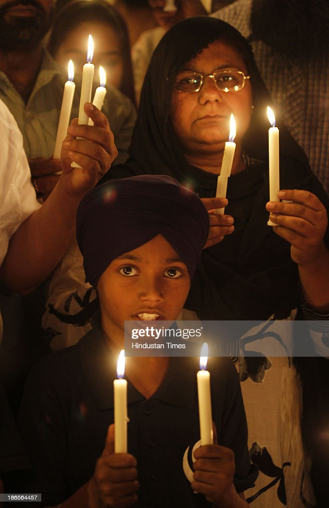 Families of 1984 Anti-Sikh riots victims holding the candle during the protest demanding justice at Jantar Mantar on November 1, 2013 in New Delhi, India. Thousands of Sikhs were killed in riots in various parts of India in November 1984 in the aftermath of the assassination of then prime minister Indira Gandhi by her two Sikh bodyguards on October 31, 1984.