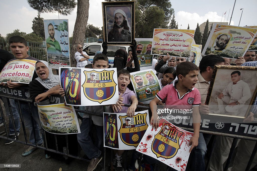 Families of Palestinian prisoners in Israeli jails hold their portraits and slogans, bearing the emblem of Spanish FC Barcelona football club, during a demonstration outside the Spanish consulate in eastern Jerusalem on October 7, 2012 to protest against Barcelona's invitation of Israeli soldier Gilad Shalit to attend today's El Clasico match. Shalit, was released on October 2011 after five years of Hamas captivity under a deal in which Israel freed more than 1,000 Palestinian prisoners in exchange.