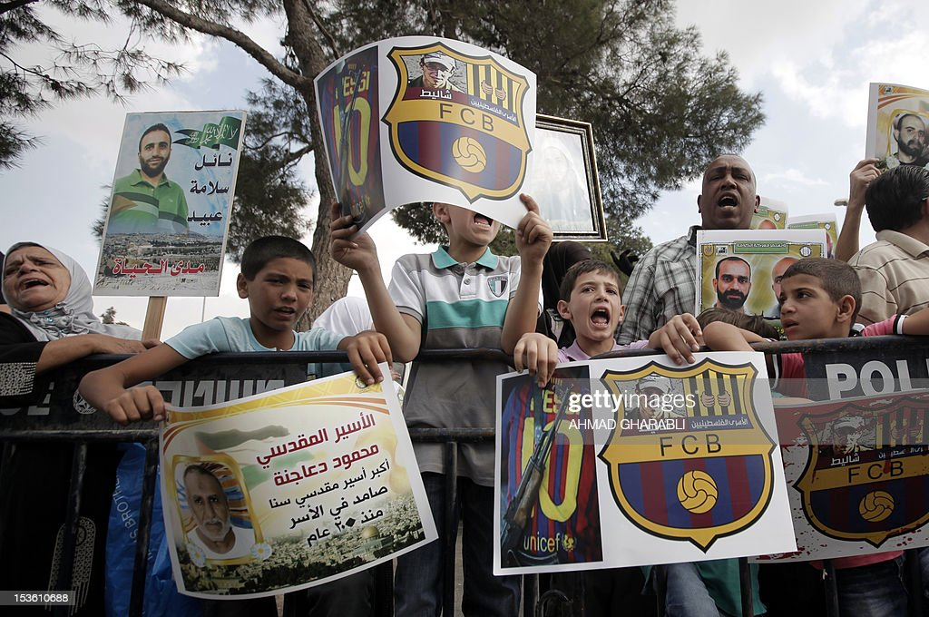 Families of Palestinian prisoners in Israeli jails hold their portraits and placards, bearing a portrait of Israeli soldier Gilad Shalit on the emblem of Spanish FC Barcelona football club, during a demonstration outside the Spanish consulate in eastern Jerusalem on October 7, 2012 to protest against Barcelona's invitation of Shalit to attend today's El Clasico match. Shalit, was released on October 2011 after five years of Hamas captivity under a deal in which Israel freed more than 1,000 Palestinian prisoners in exchange. AFP PHOTO /AHMAD GHARABLI