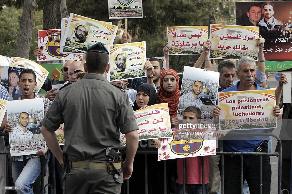 Families of Palestinian prisoners in Israeli jails hold their portraits and placards, bearing a portrait of Israeli soldier Gilad Shalit on the emblem of Spanish FC Barcelona football club, during a demonstration outside the Spanish consulate in eastern Jerusalem on October 7, 2012 to protest against Barcelona's invitation of Shalit to attend today's El Clasico match. Shalit, was released on October 2011 after five years of Hamas captivity under a deal in which Israel freed more than 1,000 Palestinian prisoners in exchange.