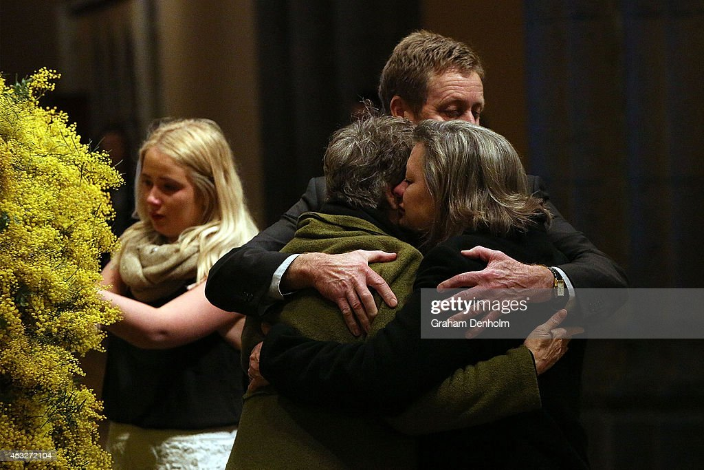 Families of the victims embrace as they leave floral tributes during a national memorial service as Australians mourn the loss of all victims of...