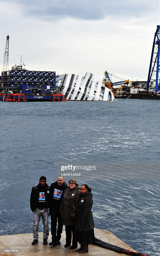 Families of two victims of the sunken Costa Concordia, 25-year-old Michel Blemand and his girlfriend 23-year-old Mylen Litzler, stand in front of the ship during a commemoration to mark the tragedy, on January 13, 2013 in Giglio Porto, Italy. A year after the sinking of the ship Costa Concordia, relatives of the victims, survivors, island residents, law enforcement and institutions gathered to mark the first anniversary and commemorate the dead. More than four thousand people were on board when the ship hit a rock off the Tuscan coast, killing 32 and leaving two people missing.