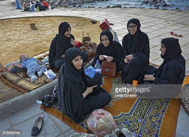 Families often gather near the famous Corniche in Jeddah Saudi Arabia for lunch These women dressed in the traditional black abayas are relaxing...